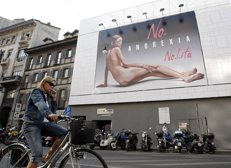 A woman rides a bicycle past an advertising board showing a shockingly emaciated naked woman in Milan