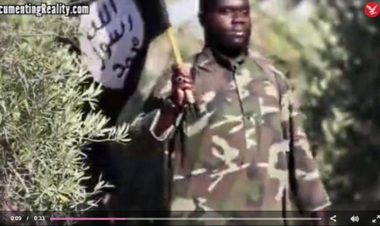 Sarfo az Iszlám Állam zászlaját viszi a terrorszervezet által közzétett propagandavideóban