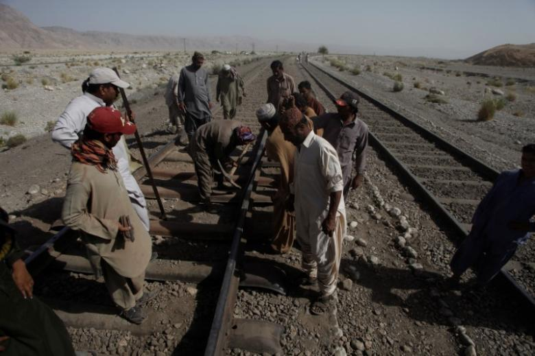Workers repair damaged rail tracks after a bomb blast attack on a train near the town of Mach in southeast of Quetta, Pakistan, October 7, 2016. REUTERS/Naseer Ahmed