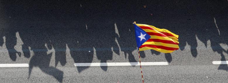 A nemzeti zászló mellett függetlenségpárti tüntetők árnyéka látszódik a barcelonai utcán. Folytatódik a huzavona Madriddal